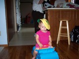 Mary, sitting on her hippo, wearing mommy's blackhawk baseball cap.