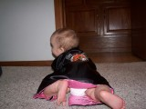 Mary crawling away from the camera.  She is wearing a silk robe that is black with pink trim.  You can see an embroidered dragon on the back and you can also see her diaper peeking out from under the robe.