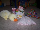 Mary's easter gifts, A big plush chickie, some stackable rings, an easter basket, some books, a dress, and some blocks.