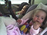 Kate and Mary sitting in their car seats each eating a graham cracker.