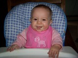 Mary sitting in her highchair with a smile and baby cereal all around her mouth.