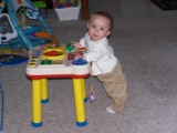 Mary standing at her play table looking sideways towards the camers.