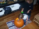Mary scooping out the pumpkin.