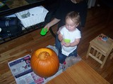 Mary standing by a pumpkin with a scoop.