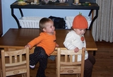 Mary and Kate at the kids table.  Kate is wearing a pumpkin hat.