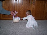 Mary crawling and reaching out to her easter bunny easter basket while mommy is holding it just out of her reach.