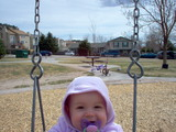 Mary sitting in the swing with her hood on and a big smile on her face.