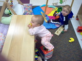 Mary standing at the bench in daycare with her feet inside a cloth box trying to lift her left foot out.