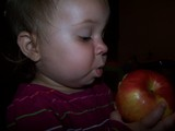 Mary with a bite of apple in her mouth staring intently at the apple.