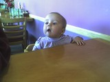Mary sitting in a highchair.  Her tongue is pushing out on her lower lip and her head is tilted back in a haughty manner.