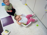 Mary in a plastic container at daycare looking confused.
