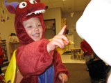 A little boy in a dragon costume pointing at Mary in her Carebear costume.