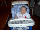 Mary sitting in her highchair smiling, maouth open, up at the camera.  She is wearing her 'I Love My Daddy' shirt.