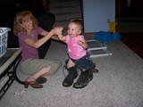 Mary putting on daddy's Army boots with mommy holding her hand.