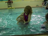 Mommy is holding Mary under her arms in the pool as if she is swimming and Mary is splashing both hands in front of her.