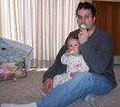 Daddy sitting on the floor with Mary in his lap.  Both are eating marshmallow Peeps.
