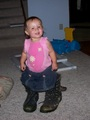 Mary in daddy's boots, standing with no help looking at the camera inquisitively.