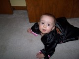 Mary on the floor in a crawling posture.  She is looking up at the camera.  She is wearing a silk robe that is black with pink trim.