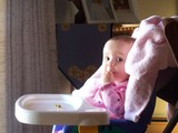 Mary sitting in her highchair eating her lunch.