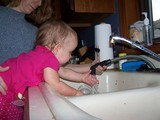 Mary reaching forward towards the sink to play in the water.