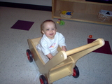 Mary sitting in the wooden cart smiling at the camera.
