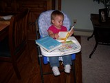 Mary sitting in her highchair reading a book.