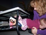 Mary crawling under the coffee table through the magazine rack.
