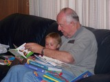 Mary and Papa sitting on the couch reading books.  Papa has 10 books stacked on his lap.