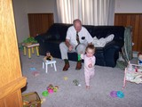 Mary in her pink pajamas running away from Papa who is dressed in a tie.