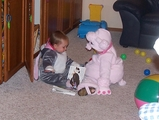 Mary in her bunny costume.  She is sitting with Kate, who is dressed in a poodle costume.  They are reading a book.