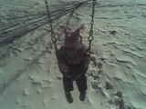 Mary in the swing at the playground.  She is wearing her winter coat and hat and there is quite a bit of snow on the ground.